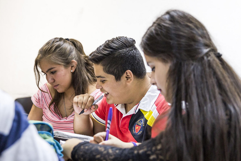 Grupo de estudiantes, tomando notas y haciendo tareas.