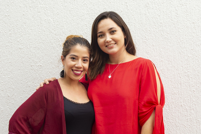 Las estudiantes  sonrien para la camara . Ambas visten de rojo