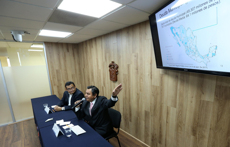 Investigador del Departamento de Administración, del Centro Universitario de Ciencias Económico Administrativas (CUCEA), doctor Clemente Hernández Rodríguez, mostrando una gasifica sobre la deuda municipal
