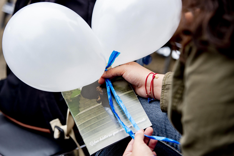 Una asistente sostiene dos globos blancos y una fotografia del estudiante asesinado