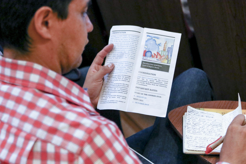 Asistente al evento, observando un triptico de la información de la maestría y de notas realizadas por el evento.