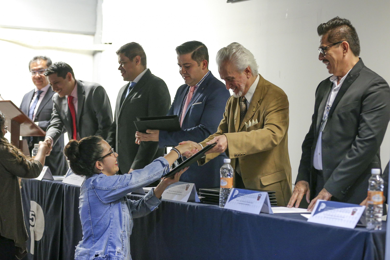 Alumna de la Preparatoria 5 de la UdeG, recibiendo reconocimiento de manos del Director del plantel.
