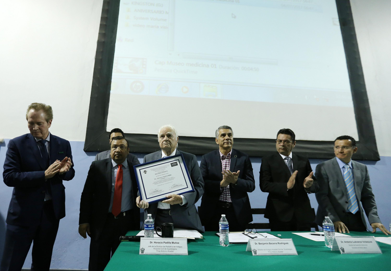 El doctor Horacio Padilla Muñoz muestra su reconocimiento al lado de los miembros de la mesa de presidium