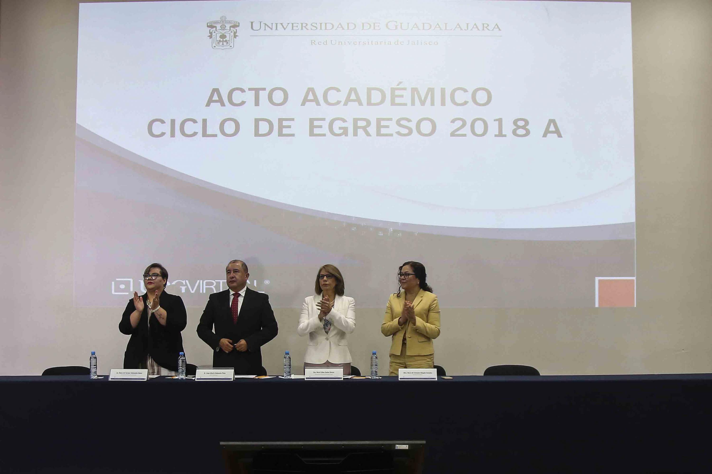 Los cuatro miembros del presidium de pie aplaudiendo durante el acto académico de egreso 2018 A