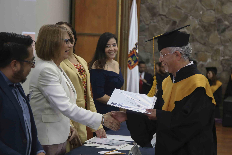 La rectora Anabel Lopez entrega su diploma a un estudiante de edad madura