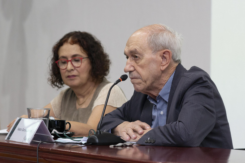 El doctor Néstor García Canclini sentado a la mesa de presidio  dio su conferencia