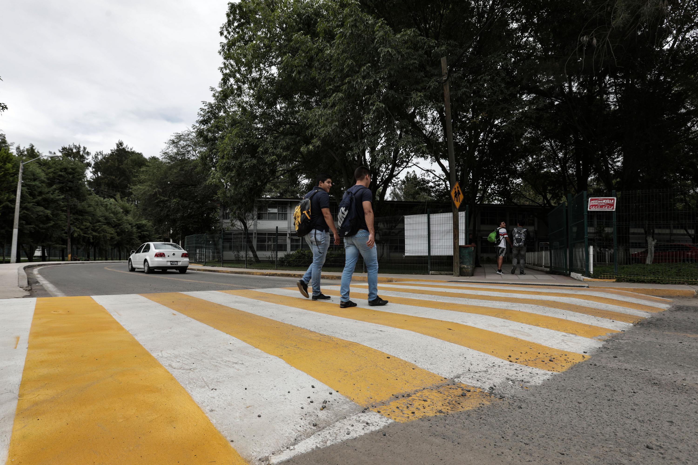 Alumnos del  Centro Universitario de Ciencias Biológicas y Agropecuarias (CUCBA), cruzando en la calle reparada