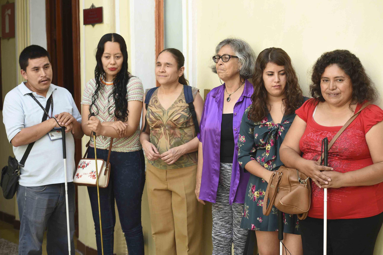 Un grupo de personas, la mayoria invidentes, esperan afuera de la sala para la inauguracion
