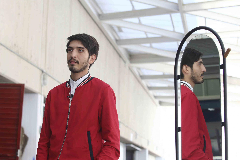 Irvyn García Rojo, egresado de la licenciatura en Diseño Industrial del CUAAD; reflejandose en el espejo de la creación de su mueble.