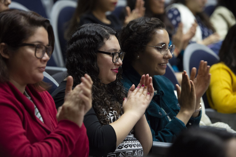 Mujeres asistentes al evento aplaudiendo