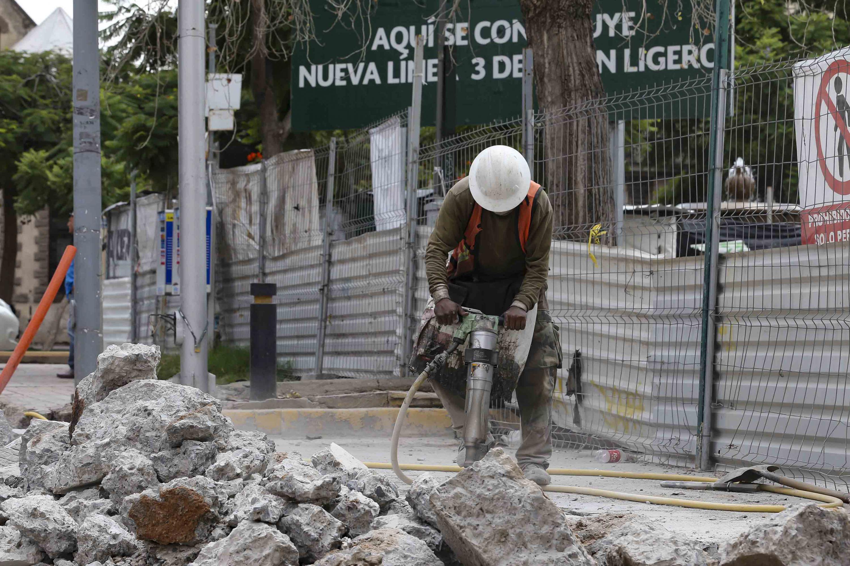 Trabajador de la construcción triturando con máquina para abrir una de las calles de la ciudad por obras del tren eléctrico de la línea 3.