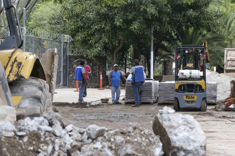 Trabajadores de la construcción platicando, mientras un trausente trata de pasar por un lado de las obras.