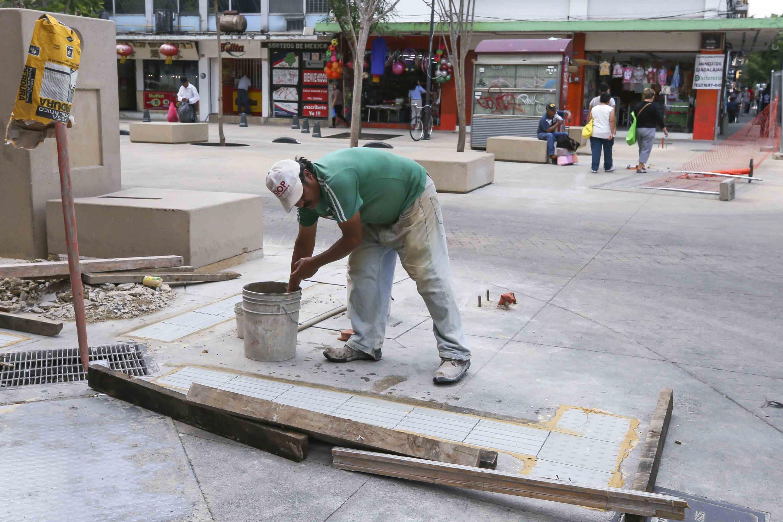 Albañil sumergiendo sus manos en balde de agua para salpicar lo que acaba de construir y pegar con cemento en la banqueta