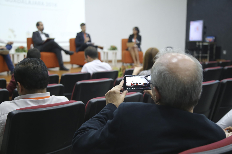 Un hombre mayor toma video con su telefono inteligente a los panelistas