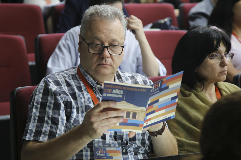Un hombre adulto lee el folleto del evento durante la conferencia
