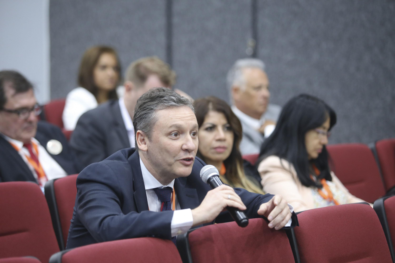 Un hombre del publico  realiza un comentario a los ponentes