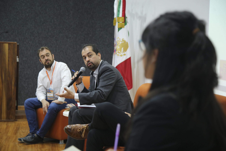 Los panelistas habando entre si para responder las preguntas del publico