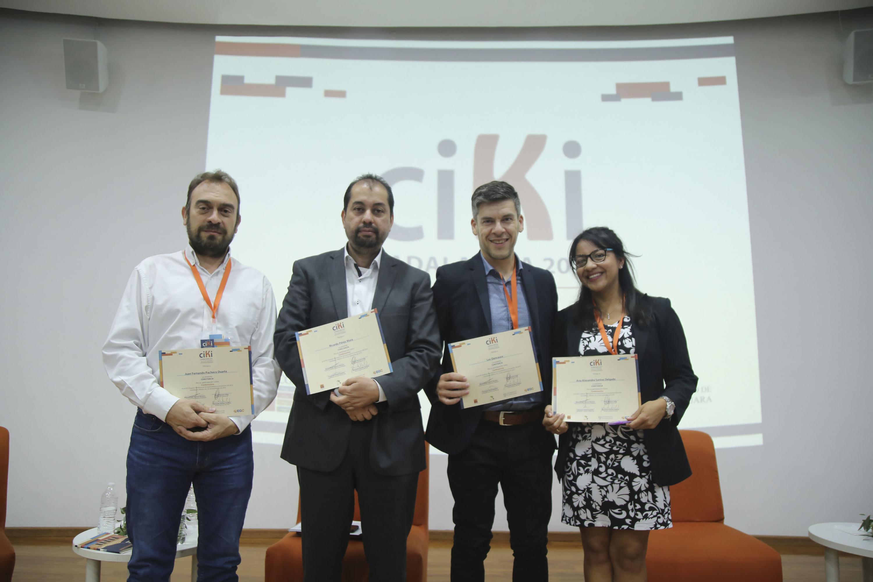Los cuatro panelistas muestran el reconocimiento impreso que les fue entregado al termino del panel