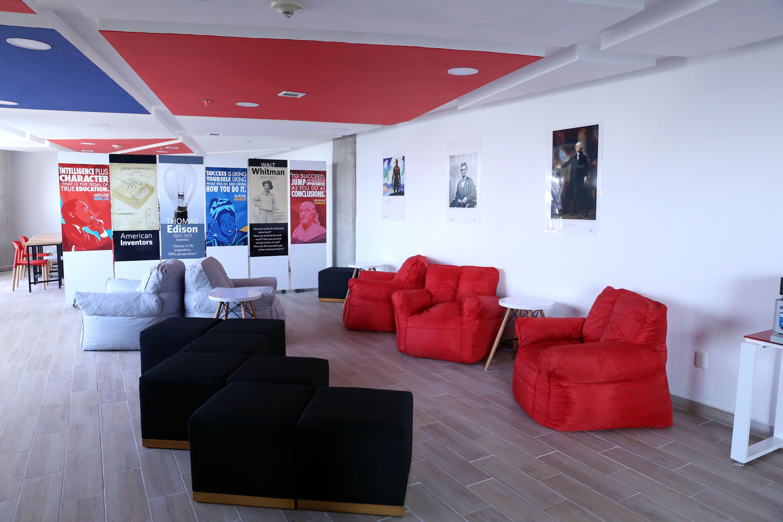 Muebles colores rojo, blanco y negro; así como, carteles de inventores, escritores, presidentes, entre otros; decoran el lugar.