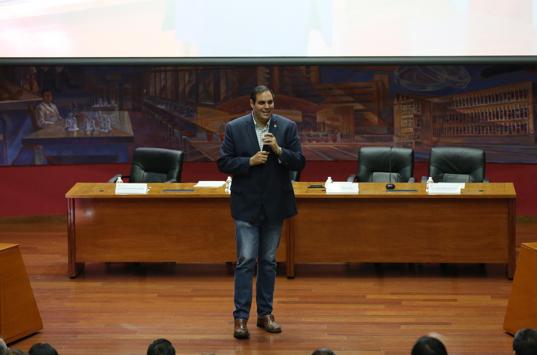 Uno de los presentadores hablando de pie hacia el publico