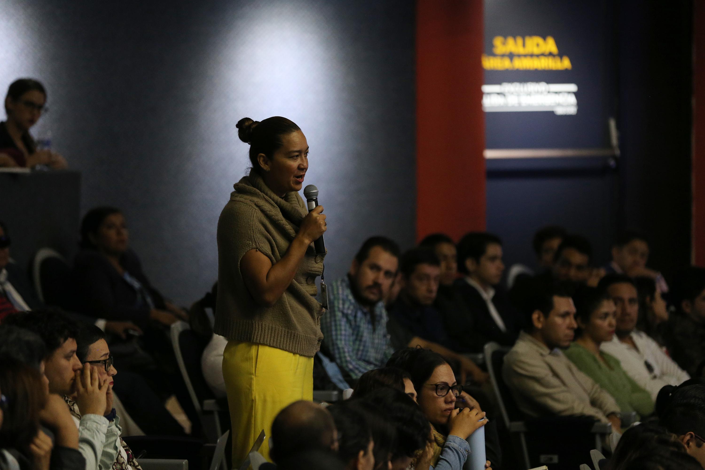 Una mujer realiza una pregunta a los conferencistas desde su lugar