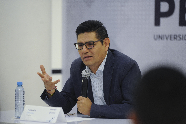 Alejandro Almazan sentado en la mesa de la conferencia
