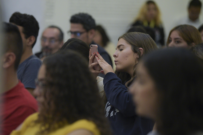 Una joven utiliza su telefono inteligente para capturar una fotografia