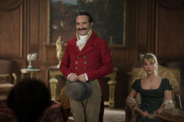 Escena de película francesa, que se traslada a la época renancentista, dónde un hombre vestido acorde a la época, se encuentra parado muy sonriente y sosteniendo su sombrero con las manos a la altura de sus caderas; en medio de dos mujeres sentadas