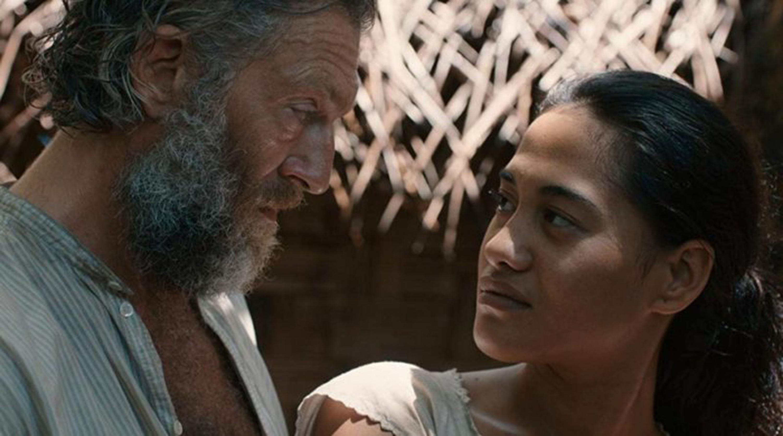Escena de cortometraje de película mexicana, dónde un hombre maduro de la tercera edad y una joven mujer morena, se encuentran mirando fijamente a los ojos.