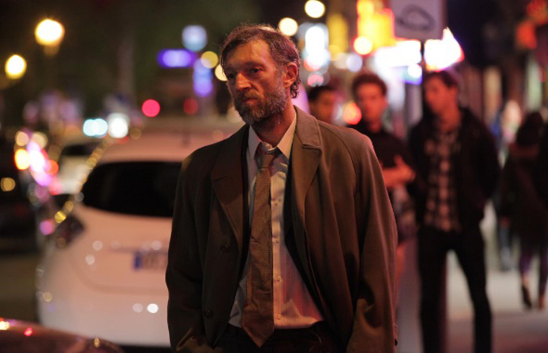 Escena de película francesa, donde un hombre maduro con barba y lleno de canas, camina en la noche por las calles de la ciudad, con las manos dentro de su pantalón y en forma de reflexión.