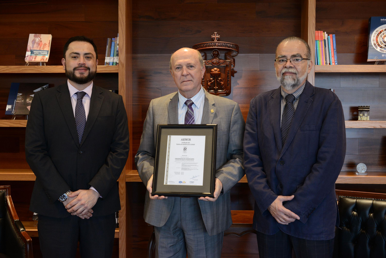 El rector general de la Universidad de Guadalajara sostiene el reconocimiento entregado a la Coordinacion de Control Escolar