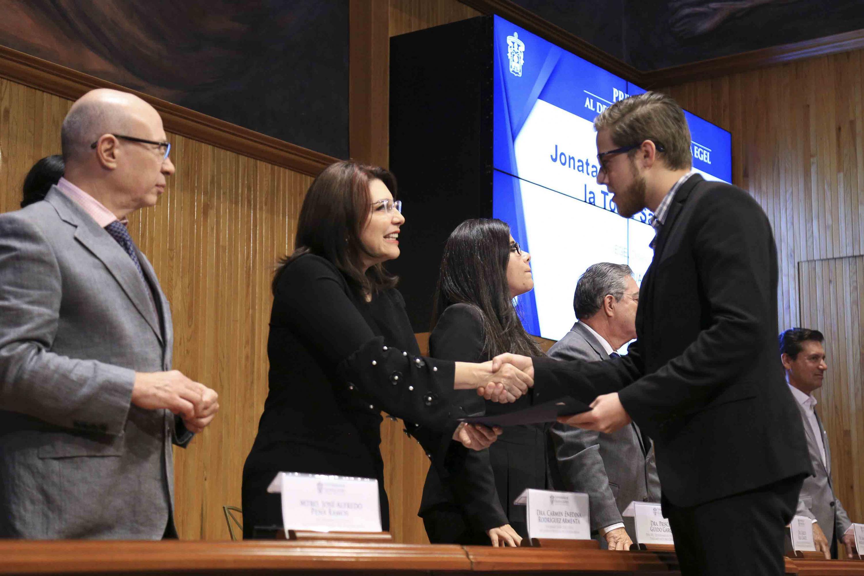 Doctora Carmen Enedina Rodríguez Armenta, Vicerrectora Ejecutiva, haciendo entrega de reconocimiento a un alumno