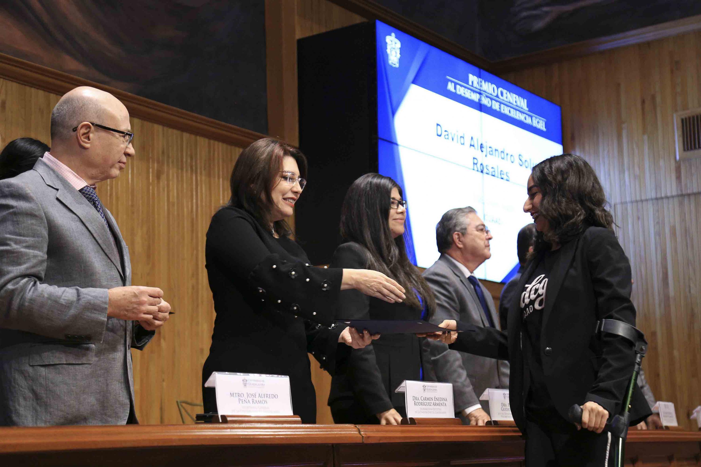 Doctora Carmen Enedina Rodríguez Armenta, Vicerrectora Ejecutiva, haciendo entrega de reconocimiento a un alumna