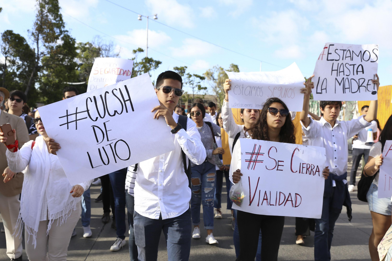 Alumnos caminando durante la marcha con carteles de CUCSH de LUTO
