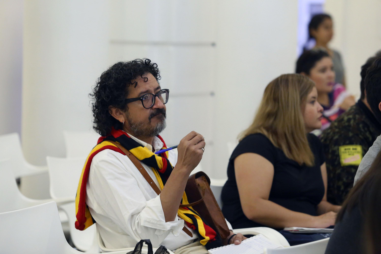 Un hombre con una bufanda de colores rojo, negro y amarillo presente en la conferencia
