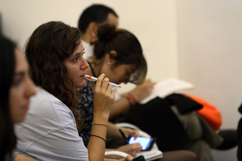 Una mujer joven escucha al conferencista desde su lugar