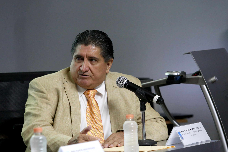 Mtro Carlos Orozco Santillan sentado en la mesa del presidium