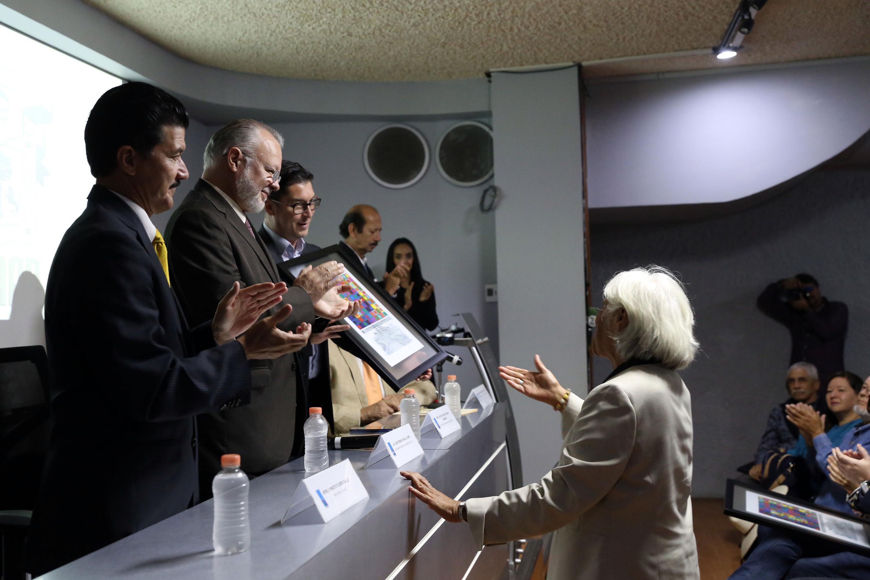 La doctora Raquel Gutiérrez Nájera recibiendo el reconocimiento de manos del maestro Padilla Lopez