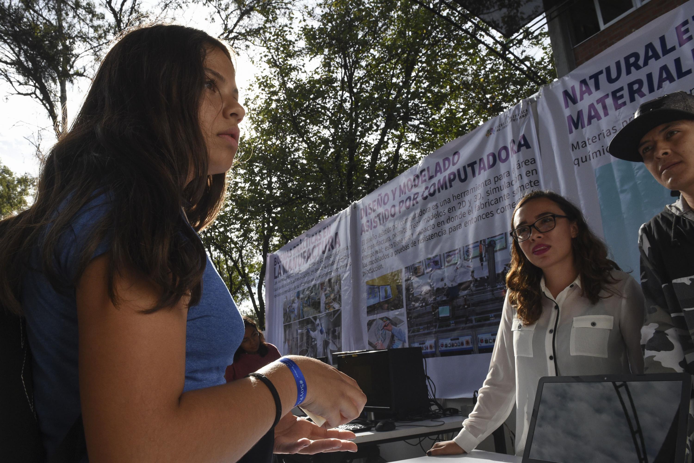 Una joven adolescente frente a una mesa de informes de varias carreras tecnicas del Poliecnico