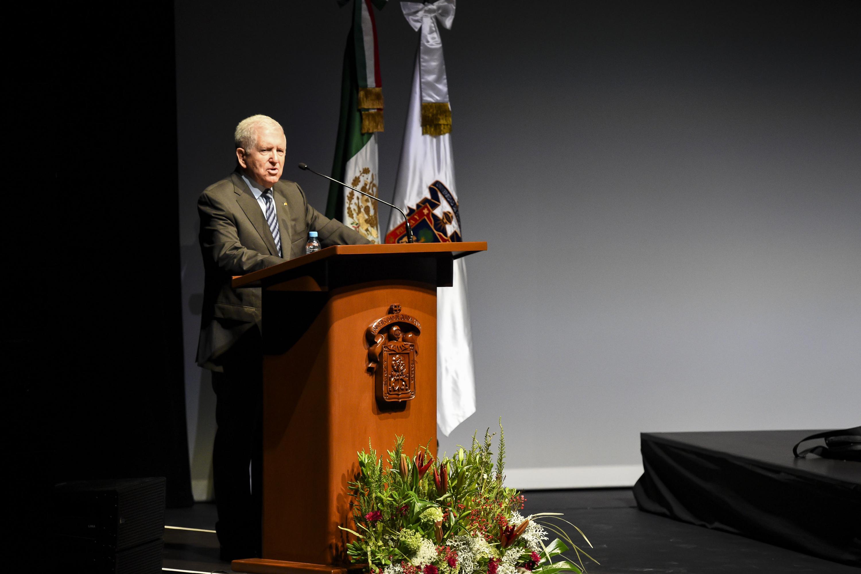 Un hombre mayor de pelo cano habla desde el podium