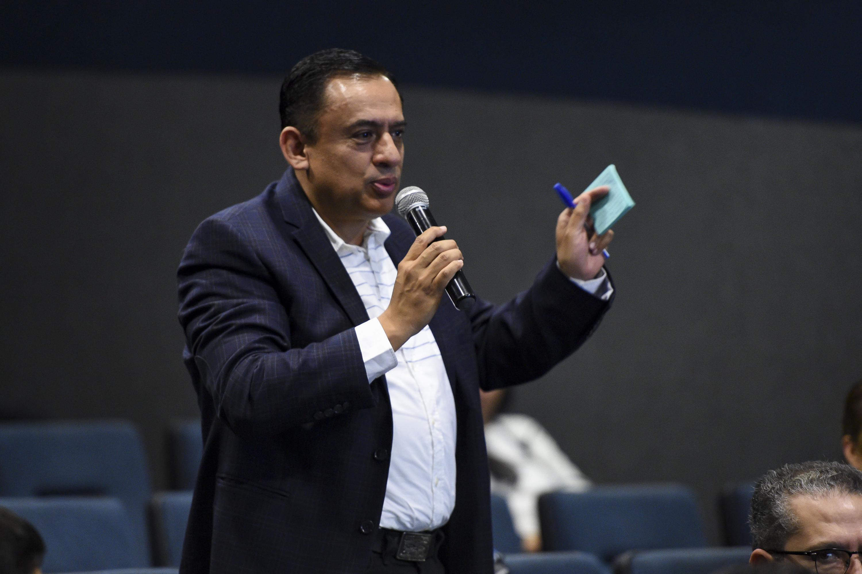 """Asistente a la conferencia magistral """"Gestión de la ciencia y la tecnología en México"""" hablando frente al microfono"""