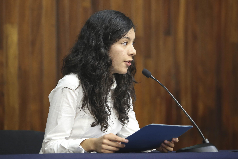 Una joven del CUCSH habla desde la mesa de presentacion al microfono