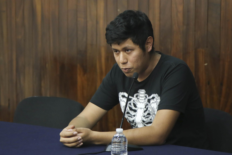Un joven con playera de esqueleto habla desde la mesa de presentación