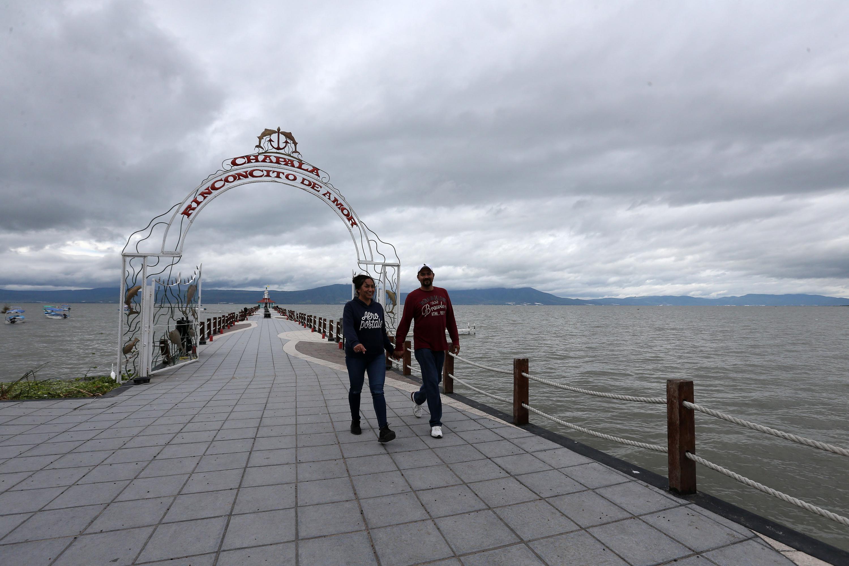 Dos personas caminando por el malecón del Lago de Chapala
