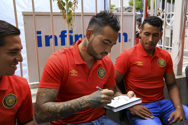 Un jugador de los leones negros firmando un autografo