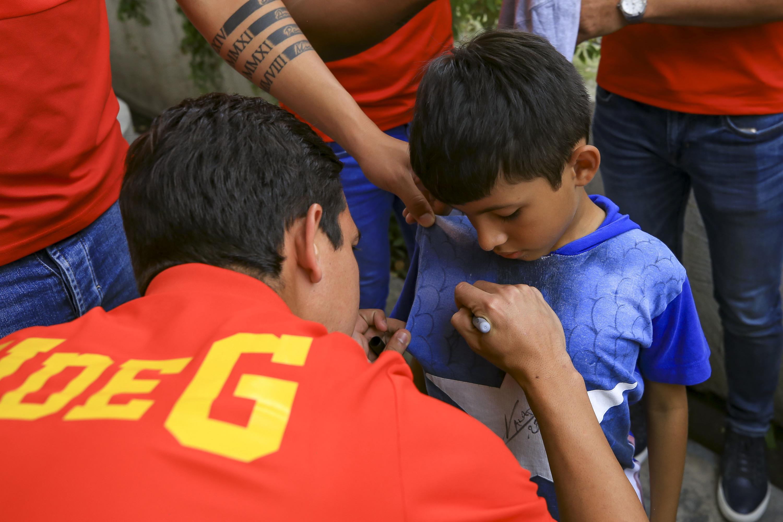 Un jugador del equipo firmando la playera de uno de los niños que asistieron
