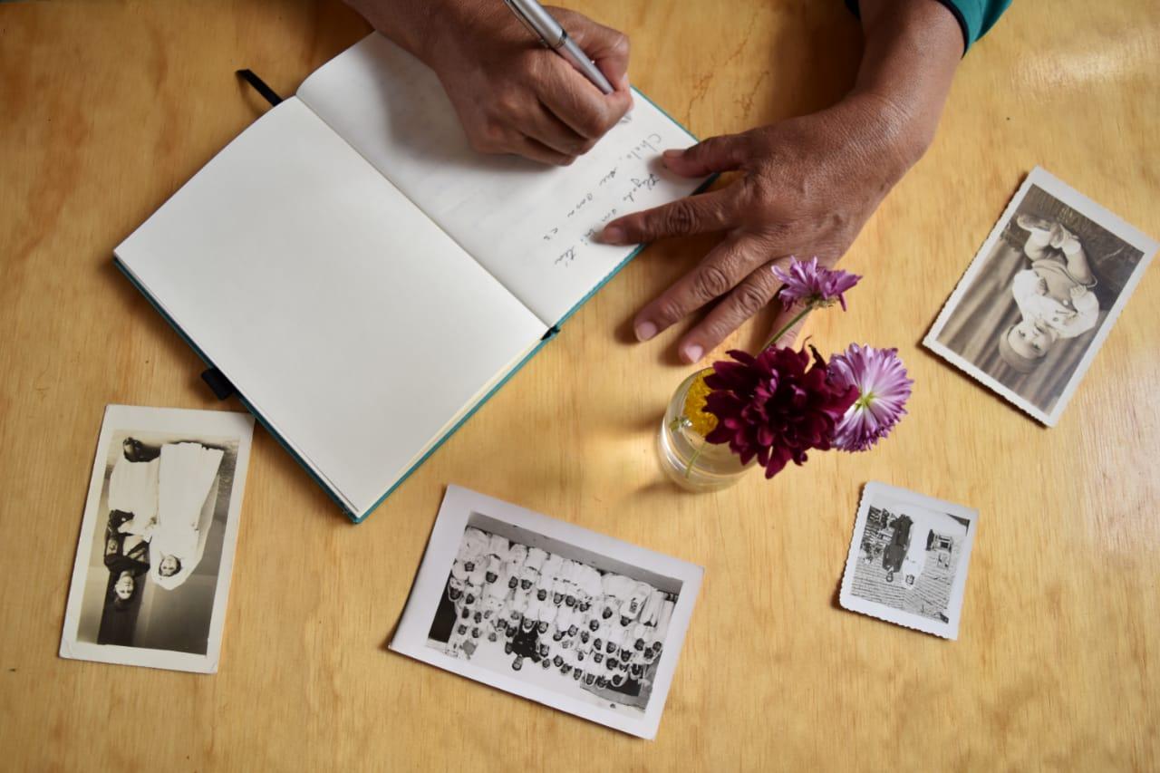 Persona adulta mayor, escribiendo en un cuaderno memorias, mientras observa 4 fotografías familiares antiguas sobre la mesa.
