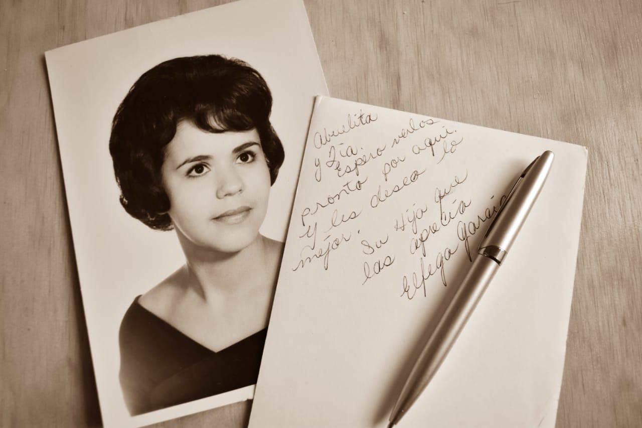 Fotografía antigua de una mujer jóven y un sobre con una escritura de saludos a familiares y una pluma, sobre la mesa.