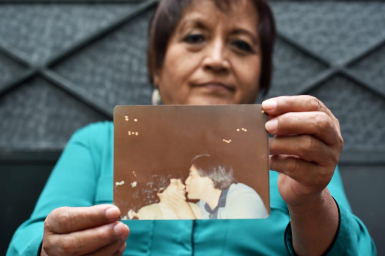 Mujer adulta, mostrando una fotografía antigua de una pareja besándose.
