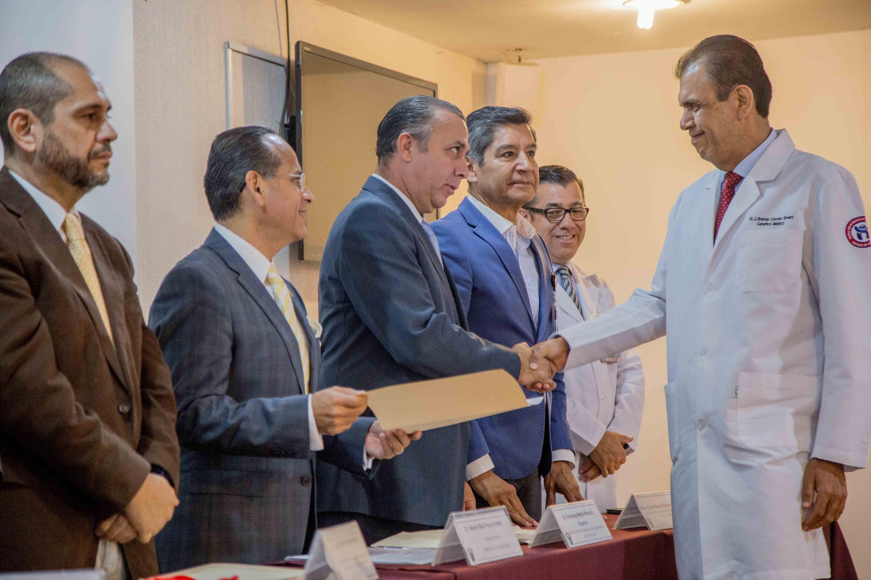 El director de los hospitales Civiles entrega a un medico su constancia desde el presidium